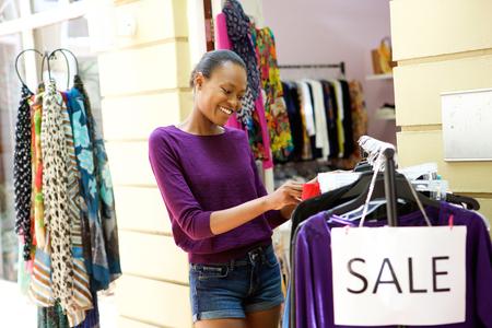 afroamericanas: Retrato de las compras felices joven mujer afroamericana para la ropa en la tienda