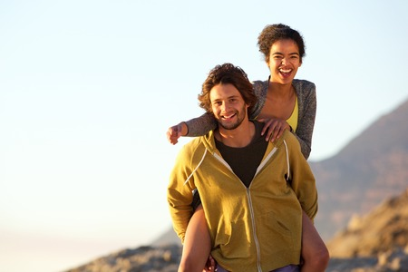 couples outdoors: Portrait of a smiling young man carrying carefree woman on back Stock Photo