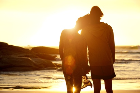 Portret van achter van liefdevolle koppel hand in hand op het strand en kijken naar de zonsondergang