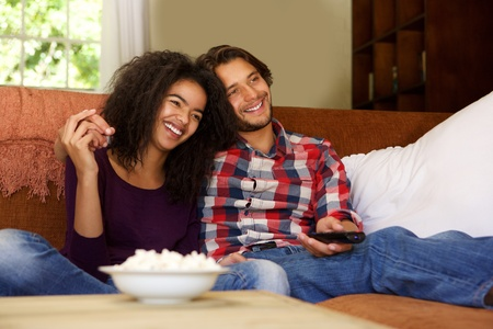 black male: Portrait of a smiling boyfriend and girlfriend relaxing at home watching tv Stock Photo
