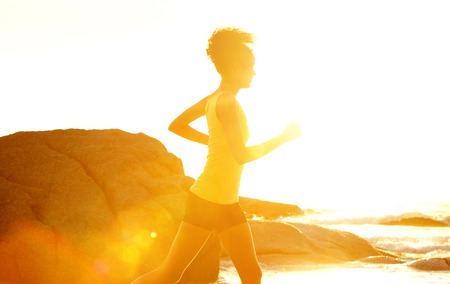 american sport: Side portrait of a young fitness woman running by the sea during sunset