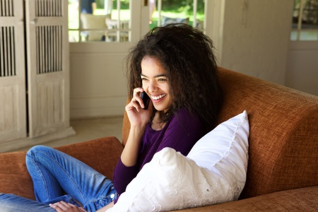 modern girls: Portrait of a smiling young woman sitting on couch talking on mobile phone