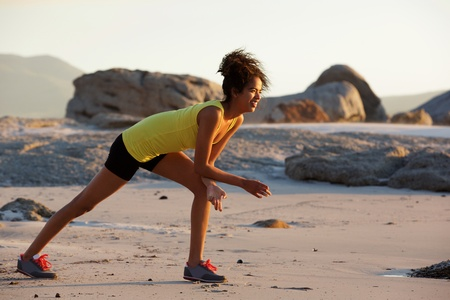 to crouch: Full length side portrait of young woman enjoying exercise on the beach Stock Photo