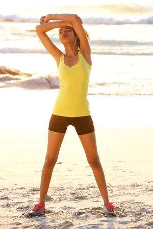 negras africanas: Retrato de cuerpo entero de una mujer de la aptitud que estira ejercicio en la playa