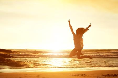 일몰 동안 해변에서 기쁨을 위해 점프 젊은 여자의 실루엣 초상화 스톡 콘텐츠