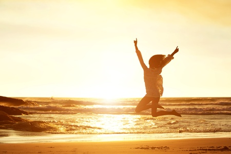 people jumping: Silhouette portrait of young woman jumping for joy at beach during sunset