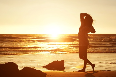 woman alone: Silhouette portrait of a young woman standing on beach Stock Photo