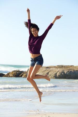 personas saltando: Retrato de cuerpo entero de un joven saltando mujer negro alegre en la playa Foto de archivo