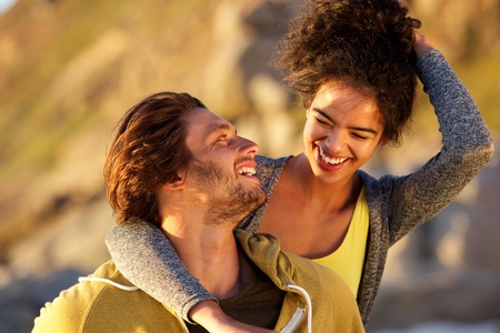 reir: Cerca de retrato de una pareja atractiva riendo juntos