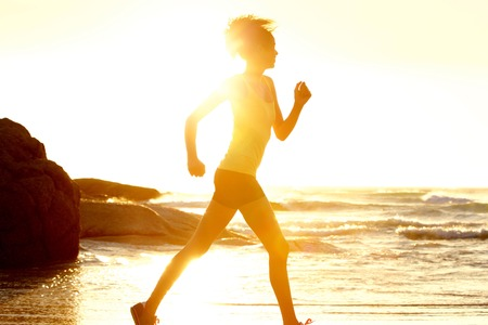 american sport: Side portrait of female runner by the sea during sunset
