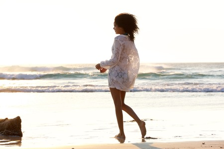 woman beach dress: Portrait of an attractive young woman walking on the beach barefoot Stock Photo
