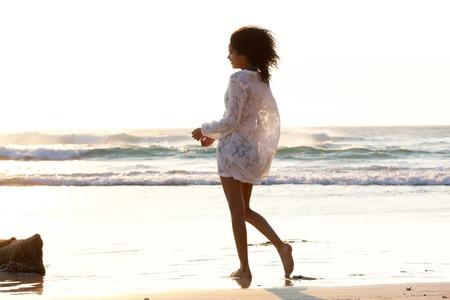 piedi nudi di bambine: Ritratto di una giovane donna attraente che cammina sulla spiaggia a piedi nudi