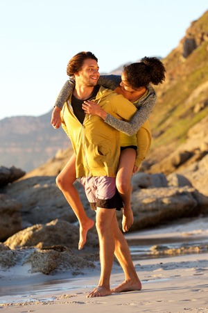 man carrying woman: Full length portrait of a young man carrying woman on his back at the beach