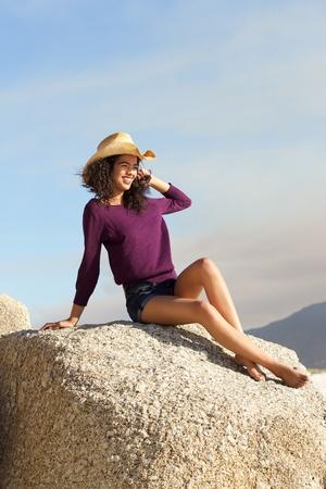 mujer sentada: Retrato de una mujer sonriente con sombrero sentado en la roca al aire libre Foto de archivo