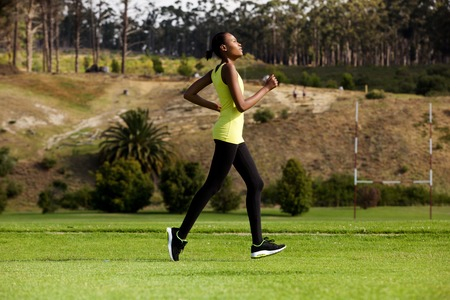 view woman: Side view full body portrait of a young woman running outdoors in a park