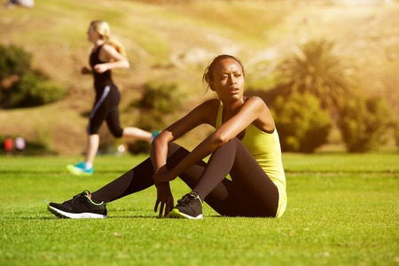 outdoor training: Portrait of young african sports woman relaxing outdoors after workout