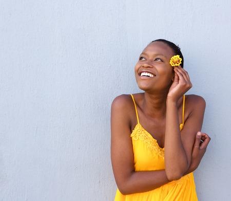 mannequin africain: Portrait de la belle jeune femme africaine tenant une fleur et en regardant loin