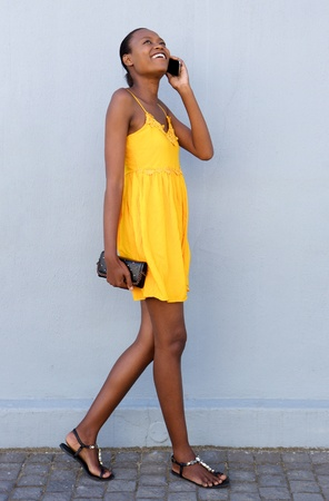people talking: Full length portrait of attractive african woman walking and talking on mobile phone