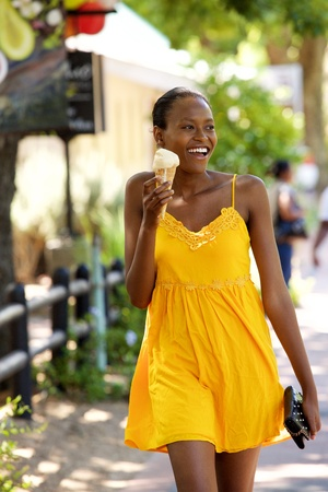 Portrait of beautiful young black woman eating ice cream on street Stock Photo