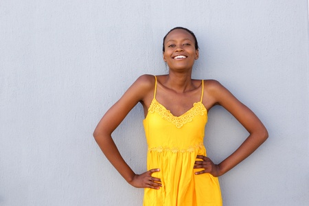 hands on hips: Portrait of attractive african woman standing with hands on her hips against gray wall