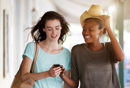 mujeres juntas: Portrait of two young women walking together and reading text message on cellphone