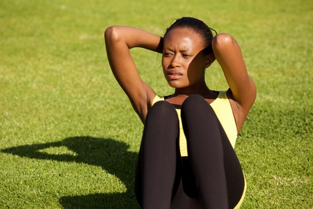 sit ups: Portrait of healthy young black woman doing sit ups outdoors on grass Stock Photo