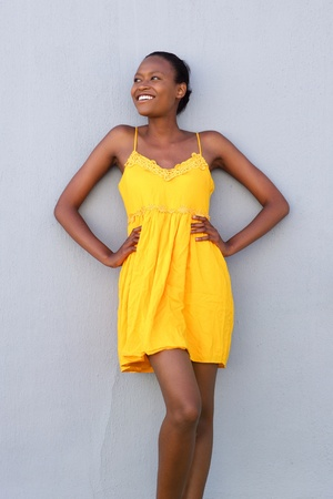 hands on hip: Portrait of a african woman smiling in elegant yellow dress against gray wall Stock Photo