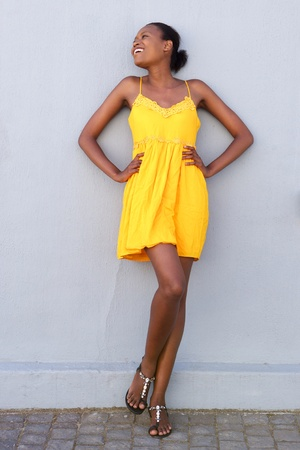 Full length portrait of a african female fashion model smiling in yellow dress