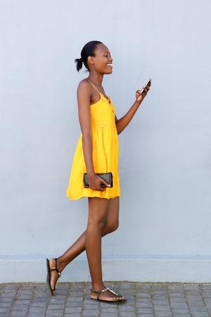 Full length kant portret van aantrekkelijke Afrikaanse vrouw lopen lezing tekstbericht op de mobiele telefoon Stockfoto