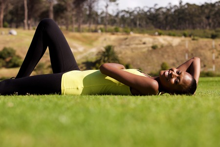lying on side: Side portrait of tired fit woman relaxing on grass at park Stock Photo