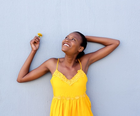 modelos negras: Retrato de la mujer africana joven en vestido amarillo que sostiene una flor contra una pared gris