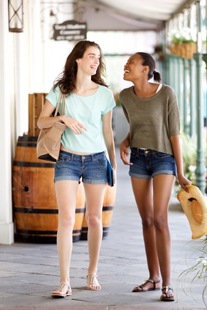 sidewalk talk: Full length portrait of happy young female friends walking together outdoors