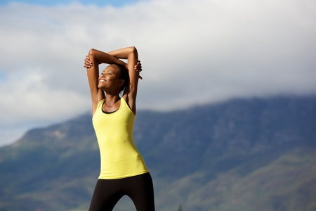 Portrait of healthy young african woman doing stretching workout in nature