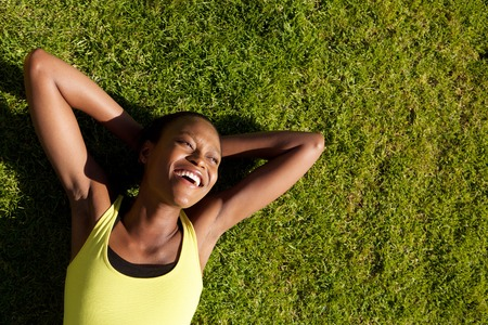 black lady: Portrait of a happy young african woman resting on grass after workout and smiling Stock Photo