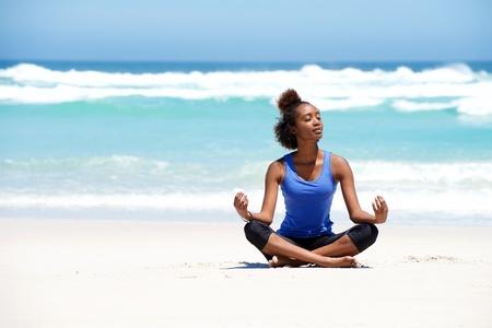 afroamericanas: Retrato de mujer joven y sana de yoga sentado en posición de loto en la playa Foto de archivo