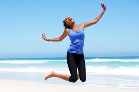 ビーチで喜びでジャンプ若いアフリカ女性の肖像画