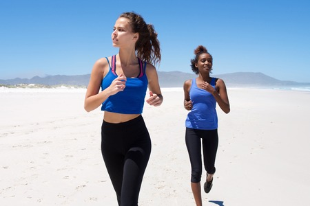 beach front: Portrait of young woman running with her friend in the background on the beach Stock Photo
