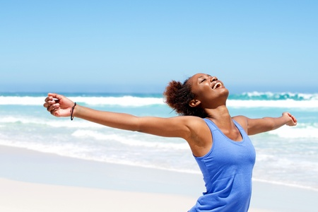 Portrait of healthy young african woman standing on the beach with her hands outstretched Stock Photo