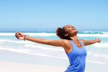 Portret van een gezonde jonge Afrikaanse vrouw die op het strand met haar uitgestrekte handen