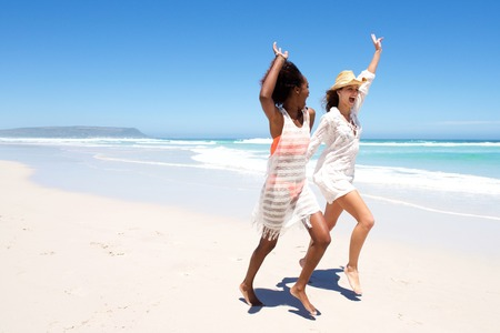 summer dress: Full body portrait of young female friends laughing and playing on the beach Stock Photo