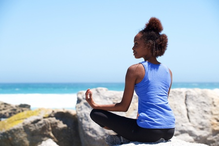vitality: Portrait of young african american woman sitting a rock at beach in yoga pose Stock Photo