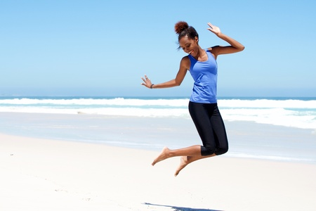 Portrait of young sporty woman jumping with joy at the beach