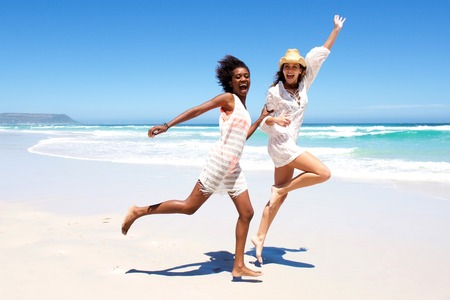 young girl barefoot: Full body portrait of two young women friends laughing and running on the beach Stock Photo