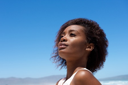 afro curly hair: Close up portrait of attractive young african woman looking away against sky outdoors Stock Photo