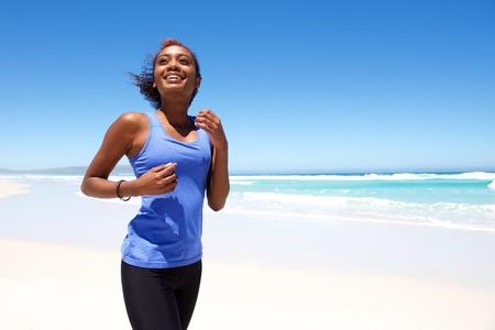 Portret van lachende jonge Afrikaanse vrouw joggen op het strand