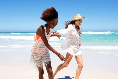 vacation: Portrait of two happy young female friends running together on beach