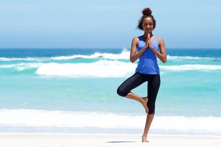 afroamericanas: Retrato de cuerpo entero de una mujer joven y sana que hace ejercicio de equilibrio yoga en la playa