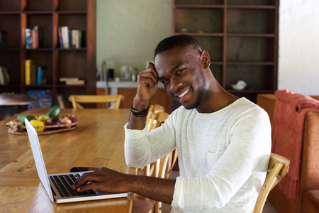 Portrait of happy young african man sitting at table with laptop at home