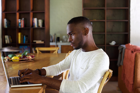 man working computer: Portrait of a young black man using laptop computer at home