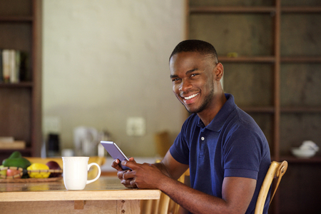 black guy: Portrait of young black guy sitting at home with a digital tablet
